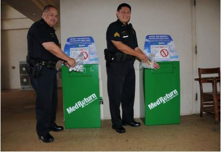 Lieutenant Scott Brede and Sgt. Sandy Wakumoto standing next to Kauai Police Department medication drop boxes.